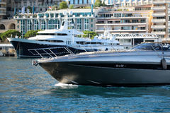 Modern motor yacht floats inshore. Monte Carlo, Monaco - September 20, 2015: yacht motor modern vessel floats on blue sea inshore on sunny summer day against Royalty Free Stock Photo