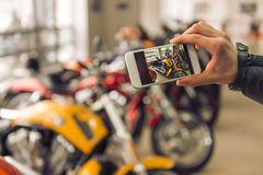 Modern motorbike salon. Man in black leather jacket is making a photo using a smart phone while standing in a motorbike salon, close-up Royalty Free Stock Images