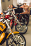 Modern motorbike salon. Man in black leather jacket is making a photo using a smart phone while standing in a motorbike salon, close-up Royalty Free Stock Image