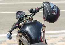 Modern motorcycle cafe racer and black helmet on a city street close up. Modern motorcycle cafe racer and black helmet on a city street closeup royalty free stock photography