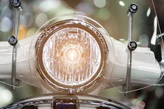 Modern motorcycle headlight with bokeh in night city street. Royalty Free Stock Images