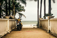 Modern motorcycle on pavement of beach. Back view of motorbike parked on pavement under palms on background of Kamala beach Stock Images