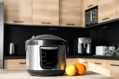 Modern multi cooker and ingredients on table in kitchen royalty free stock images