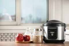 Modern multi cooker and products on table in kitchen. Space for text stock photo