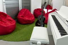 Modern music-room, with white piano and black guitar; red beanbags in the background Royalty Free Stock Images