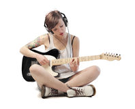Modern musician. Isolated seated young woman playing electric guitar royalty free stock images