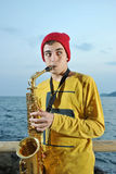 Modern musician posing with his saxophone Stock Images