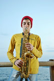 Modern musician posing with his saxophone Stock Photography