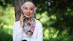 Modern Muslim girl talking on mobile outdoor stock video