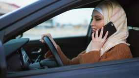 Modern Muslim woman having a phone talk at the wheel. Slow motion shot of young Muslim woman wearing a headscarf talking on mobile phone before going for a ride stock footage