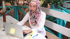 A modern Muslim woman in a hijab prints a letter to a business partner on laptop stock video