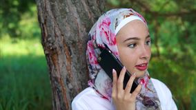 A modern Muslim woman speaks on a smartphone, she sits near a tree in the park stock footage