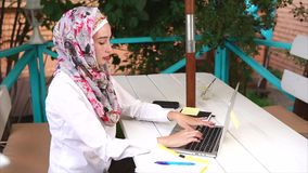 A modern Muslim woman wearing a hijab prints message to her friends on a laptop stock footage