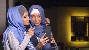 Modern Muslim women take pictures on a mobile phone. Girls in hijabs talking and smiling.  stock video