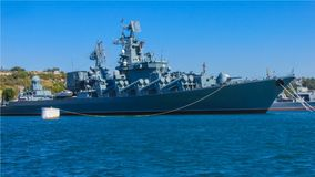 Modern naval forces. A gray warship equipped with the latest weapons. On board are complex instruments, antennas. Military base, flotilla. Sea harbor, sunny day Stock Image