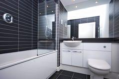 Modern new bathroom in black and white. Modern family en-suite bathroom in black and white with large bath tub, white ceramic wash basin and toilet Stock Photo