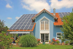 Modern new built house and garden, rooftop with solar cells, blu Royalty Free Stock Images