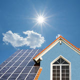 Modern new built house, rooftop with solar cells, bright sunshin. Modern new built house, rooftop with solar cells, blue front and bright sunshine Royalty Free Stock Image