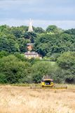 Modern new holland combine harvester cutting crops. Corn wheat barley rape oilseed working field with house and church Stock Image