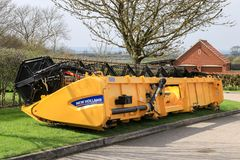 A modern New Holland combine harvester header. Modern new holland yellow combine harvester header used for cutting crops oilseed rape working the field corn Royalty Free Stock Photos