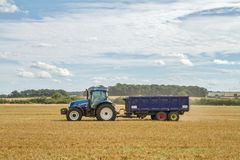 Modern New Holland tractor pulling blue trailer Royalty Free Stock Images