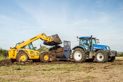 Modern New Holland tractor Tractor being loaded up with muck for muck spreading Stock Photo