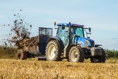 Modern New Holland tractor Tractor spreading manure on fields. A blue new holland tractor Tractor spreading manure muck on fields Stock Images