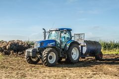 Modern New Holland tractor Tractor spreading manure on fields Stock Photos