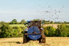 Modern New Holland tractor Tractor spreading manure on fields. A blue new holland tractor Tractor spreading manure muck on fields Royalty Free Stock Photo
