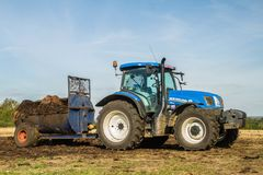 Modern New Holland tractor Tractor spreading manure on fields Stock Images