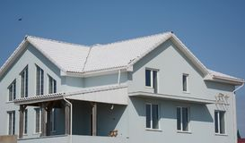 Modern house building with white tiled roof. Modern new house building with white tiled roof royalty free stock photo