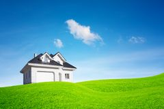 A modern, newly built white house, with a garage in front. House on a green glade under a blue sky.  royalty free stock image