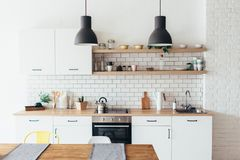 Modern nieuw licht binnenland van keuken met witte meubilair en eettafel stock foto's