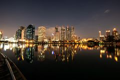 Modern night city skyline with lights reflection stock images
