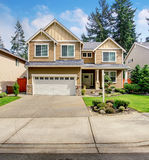 Modern northwest home with tan exterior, and garage. Stock Photography