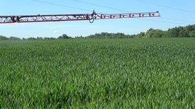 Modern ny åkerbruk traktor som besprutar skördfältet i sommartid stock video