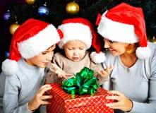 Modern och barn med gåvan för det nya året på julen semestrar Fotografering för Bildbyråer