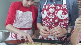 Modern och barn skrattar i processen av att förbereda julkakan lager videofilmer