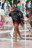 Modern och barnet får blött spela i Atlanta parkerar springbrunnen Royaltyfria Foton