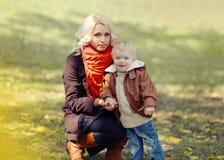 Modern och barnet går i höst Royaltyfri Bild