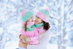 Modern och barnet i stack vinterhattar spelar i snö på familjen som jul semestrar Handgjord ullhatt och halsduk för mamma och ung royaltyfri fotografi