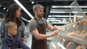 Modern och barnet köper bakad rulle i supermarket, sätter ger representanten i förkläde mat i plastpåse och den till arkivfilmer