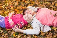Modern och barnet kopplar av att lägga på höstliga sidor Royaltyfri Fotografi