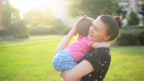 Modern och barnet kramar och har roligt utomhus- i naturen, lycklig gladlynt familj Fostra och behandla som ett barn att kyssa oc arkivfilmer
