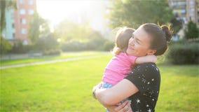 Modern och barnet kramar och har roligt utomhus- i naturen, lycklig gladlynt familj Fostra och behandla som ett barn att kyssa oc
