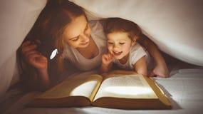 Modern och barnet läste boken under filten med en ficklampa Royaltyfria Foton