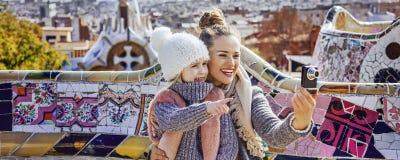 Modern och barnet med den digitala kameran som tar fotoet på Guell, parkerar Royaltyfria Bilder
