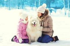 Modern och barnet med vit Samoyed dog tillsammans på insnöad vinter Arkivbilder