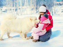 Modern och barnet med vit Samoyed dog tillsammans på insnöad vinter Arkivfoto