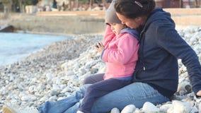 Modern och barnet sitter på stranden och tycker om solnedgången stock video